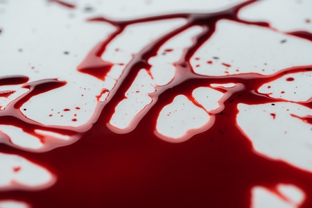 Photo for close-up shot of messy blood droplets on white surface - Royalty Free Image