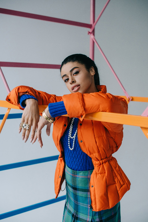 Photo pour young stylish african american female model in fashionable orange winter jacket posing near colorful scaffold in studio - image libre de droit