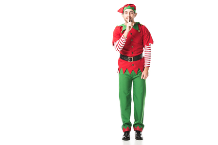 Photo for smiling man in christmas elf costume showing hush silence sign and looking at camera isolated on white - Royalty Free Image