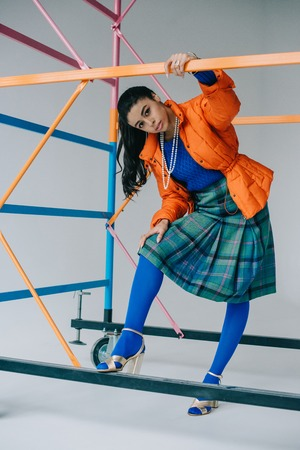 Photo pour stylish girl in orange winter jacket, checkered skirt and blue tights posing near colorful scaffold in studio - image libre de droit