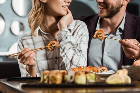 Foto de Cropped view of smiling happy couple eating sushi in restaurant - Imagen libre de derechos