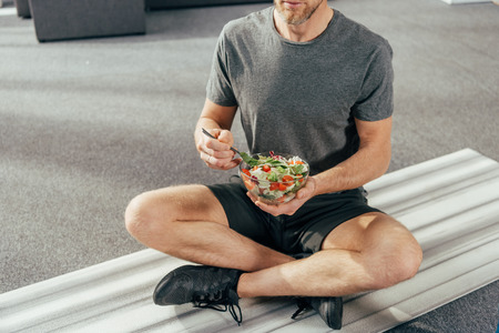 Foto de cropped shot of athletic man in sportswear sitting on yoga mat and holding bowl with vegetable salad at home - Imagen libre de derechos