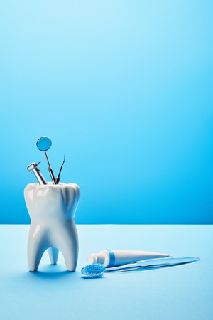Photo pour close up view of white tooth model, toothbrush, toothpaste and stainless dental instruments on blue backdrop - image libre de droit