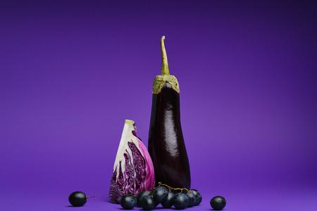 Photo pour close-up view of sliced cabbage, grapes and eggplant on purple - image libre de droit