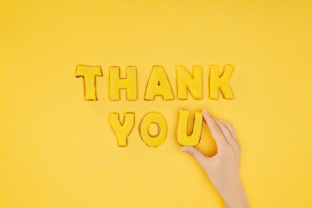Foto de cropped view of hand adjusting thank you lettering in cookies isolated on yellow background - Imagen libre de derechos