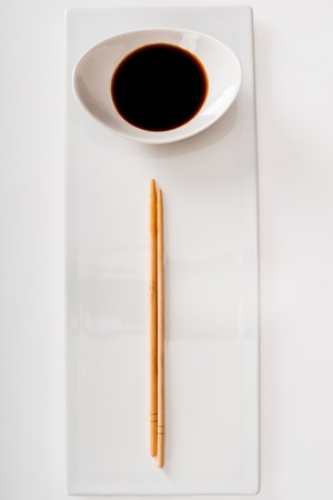 Photo pour Top view of plate with soy sauce and chopsticks on white slate - image libre de droit