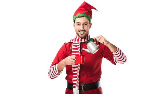 Photo for happy man in christmas elf costume with metal kettle pouring tea in cup and looking at camera isolated on white - Royalty Free Image