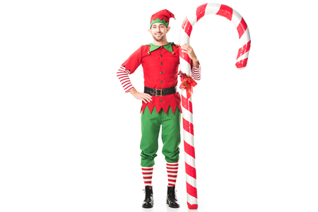 Photo for smiling man in christmas elf costume with hand on hips standing near big candy cane isolated on white - Royalty Free Image