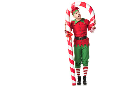 Photo pour surprised man in christmas elf costume standing under big candy cane isolated on white - image libre de droit