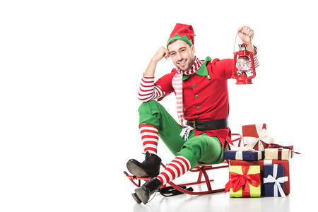 Photo for man in christmas elf costume sitting on sleigh near pile of presents and holding red lantern isolated on white - Royalty Free Image