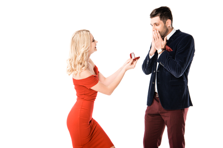 Photo pour Attractive woman proposing surprised boyfriend with ring isolated on white - image libre de droit
