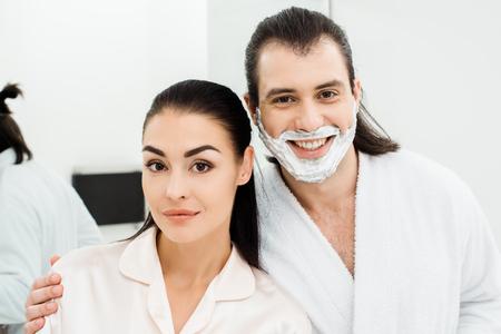 Photo pour Close up of cute smiling couple in white bathrobes - image libre de droit