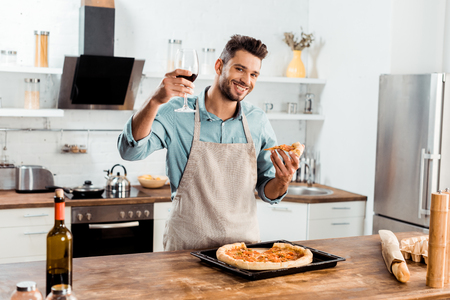Foto de smiling young man in apron holding close of homemade pizza and glass of wine - Imagen libre de derechos