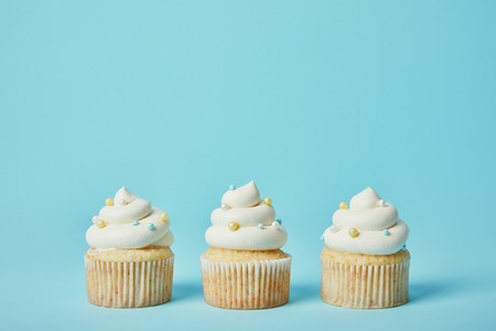 Photo pour Tasty cupcakes with sugar sprinkles on blue background - image libre de droit