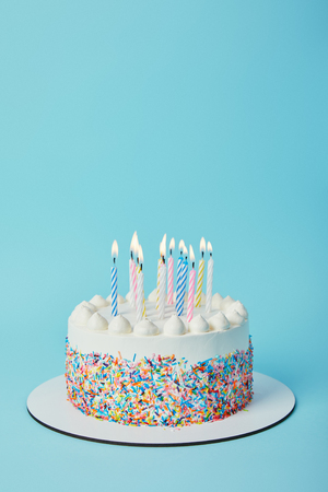 Foto de Tasty birthday cake with lighting candles on blue background - Imagen libre de derechos