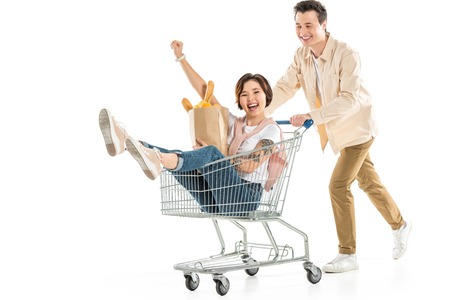 Foto de smiling husband pushing shopping cart with wife inside holding groceries isolated on white, couple having fun - Imagen libre de derechos