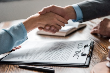 Foto de close-up view of clipboard with contract and lawyer with client shaking hands behind - Imagen libre de derechos