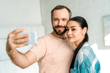 beautiful happy couple taking selfie on smartphone