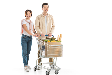 Photo pour happy young couple with shopping cart full of groceries looking at camera isolated on white - image libre de droit