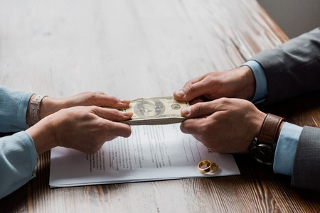 Photo for partial view of lawyer and client holding dollar banknotes above divorce decree with wedding rings - Royalty Free Image