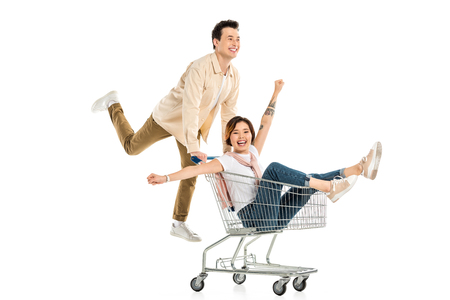 Foto de happy husband pushing shopping cart with wife inside isolated on white, couple having fun - Imagen libre de derechos