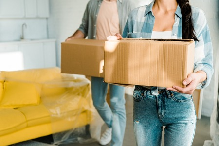 Photo pour cropped view of husband and wife carrying cardboard boxes and packing for new house, moving concept - image libre de droit