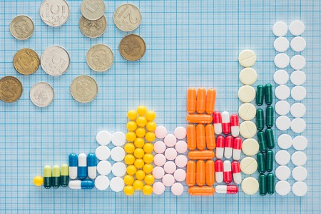 Foto de view from above of arranged stacks of colorful pills and russian rubles on blue checkered surface - Imagen libre de derechos