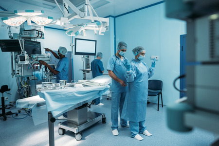 Foto de doctor helping to wear surgical uniform in operating room - Imagen libre de derechos