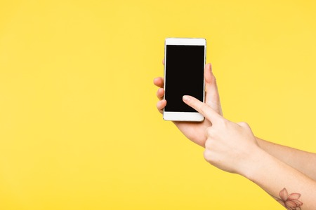 Photo for cropped shot of person holding smartphone with black screen isolated on yellow - Royalty Free Image