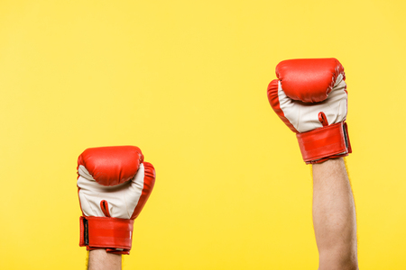 Foto de cropped shot of person in boxing gloves isolated on yellow - Imagen libre de derechos