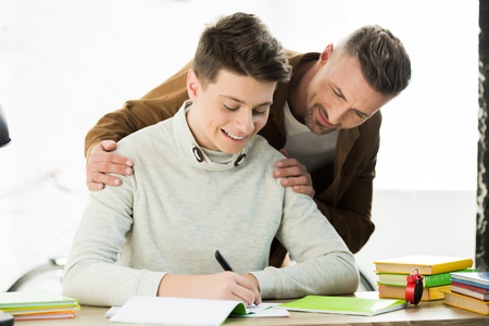 Foto de smiling father hugging teen son while he doing homework and writing something - Imagen libre de derechos