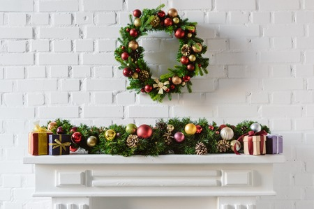 Photo for christmas wreath and decorations over fireplace mantel with white brick wall - Royalty Free Image