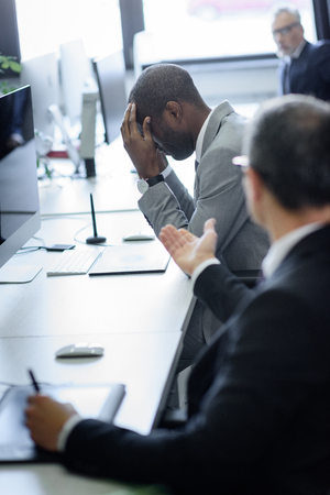 Foto de selective focus of stressed african american businessman and arguing colleague in office - Imagen libre de derechos