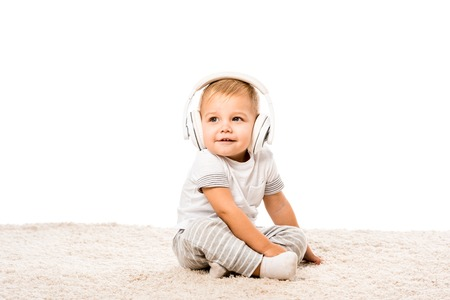 Photo for toddler boy sitting on carpet with headphones isolated on white - Royalty Free Image