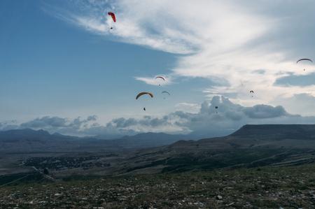 Foto de Parachutists gliding in blue sky over scenic landscape of Crimea, Ukraine, May 2013 - Imagen libre de derechos