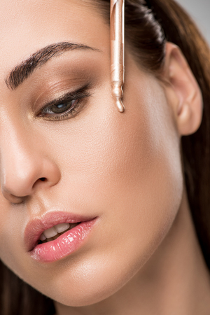 Foto de attractive girl applying highlighter or bronzer with pipette - Imagen libre de derechos