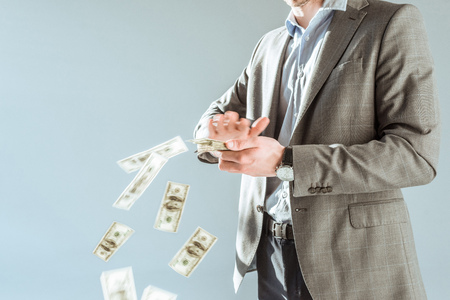 Foto de Close-up view businessman throwing money isolated on grey - Imagen libre de derechos