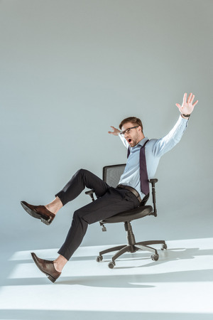 Foto de Excited stylish businessman sitting on chair with hands and legs outstretched - Imagen libre de derechos
