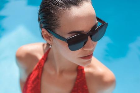 Photo pour close-up portrait of young wet woman in bikini at swimming pool - image libre de droit