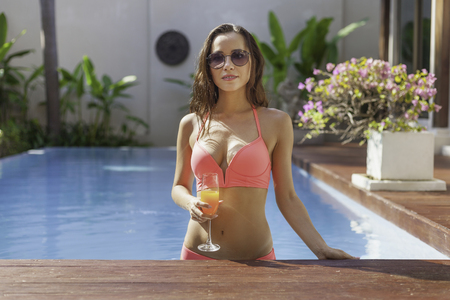 Photo pour attractive young woman in bikini at poolside - image libre de droit
