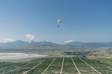 Foto de Mountainous landscape with paratrooper flying in the sky, Crimea, Ukraine. - Imagen libre de derechos