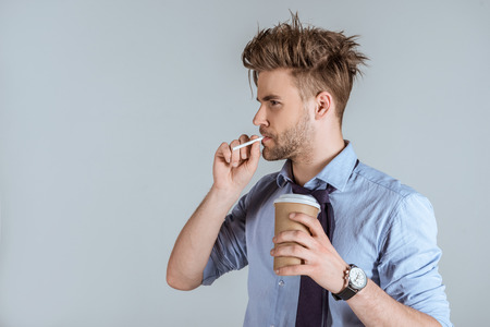 Foto de Tired businessman holding paper cup and smoking cigarette isolated on grey - Imagen libre de derechos