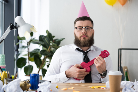 Photo pour portrait of businessman with party cone on head and toy guitar at workplace in office - image libre de droit