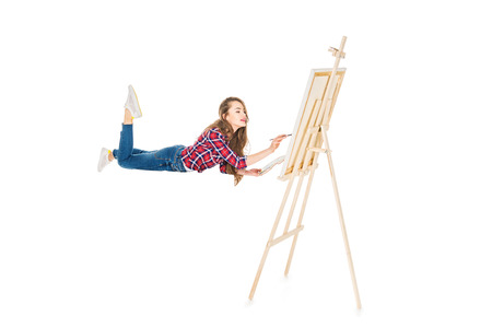 Foto de girl levitating and painting on easel isolated on white - Imagen libre de derechos