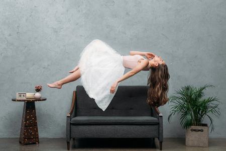 Foto de beautiful young barefoot woman levitating above couch - Imagen libre de derechos