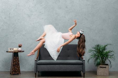 Foto de young barefoot woman in virtual reality headset levitating above couch - Imagen libre de derechos