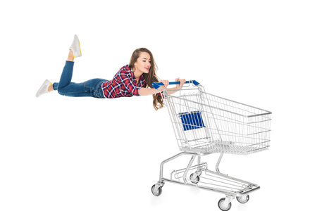 Foto de smiling young woman levitating with empty shopping trolley isolated on white - Imagen libre de derechos