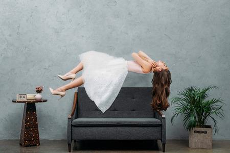 Foto de beautiful barefoot girl hovering above couch - Imagen libre de derechos