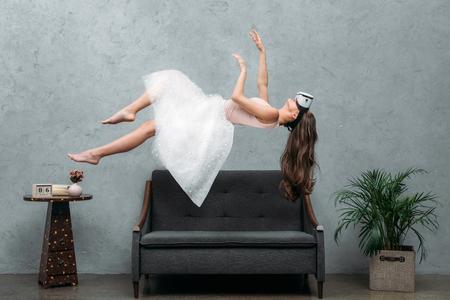 Foto de beautiful  barefoot girl in virtual reality headset levitating above couch - Imagen libre de derechos