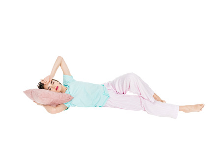 Foto de girl in pajamas lying on pillow with closed eyes isolated on white - Imagen libre de derechos